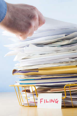filing documents: Business image of a male hand with blue shirt cuff visible, adding or removing document from tall pile in overflowing office filing tray.
