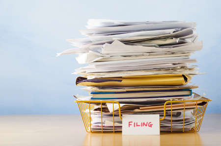 An old yellow wireframe filing tray, piled high with documents and folders, on a light wood veneer desk against light blue background  Banque d'images