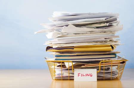 Un vieux jaune plateau de dépôt filaire, empilés avec des documents et des dossiers, sur un bureau en placage de bois clair sur fond bleu clair Banque d'images