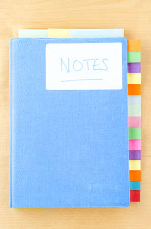 organising: A light blue fabric textured notebook, labeled with the handwritten word Notes. Down the right hand sized and along the top edge are a variety of colourful, blank sticky tabs left blank to provide copy space.