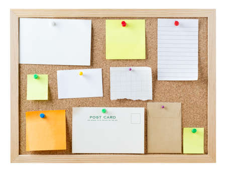 pinned: A cork pinboard, isolated on white, with a variety of pushpins sticky notes, cards and pieces of paper, left blank to provide copy space for messages.