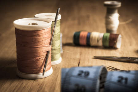 An old style image of cotton reels and other sewing items on a wooden table. Image has been aged to give a retro or vintage style. photo