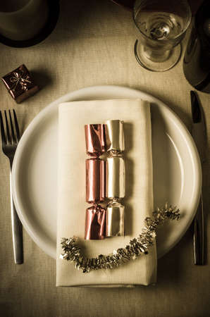 Overhead shot of a Christmas table setting with shiny foil crackers and starry tinsel on a dinner plate with a small gift box for the diner.  A, wine glass and bottle and a candle sit at top of frame. photo