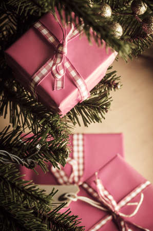 Pink Christmas gift boxes in branches and around base of decorated tree, wrapped in gingham ribbon and tied with bows.  Shot from above and looking downwards through branches to the wood laminate floor. photo