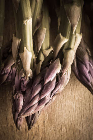 saturation: Close up, overhead shot of asparagus spear tips on wooden board with retro or vintage style colour saturation and vignette.