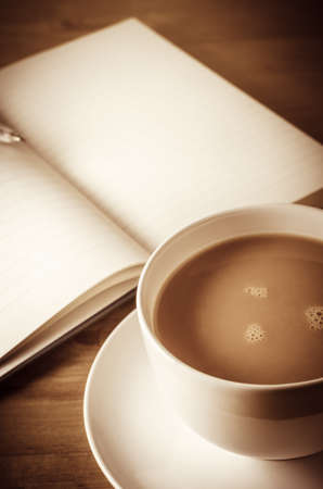 free thought: A cup of tea in the foreground with opened journal in softer background revealing blank lined pages and pen resting on top.  Wooden table underneath.