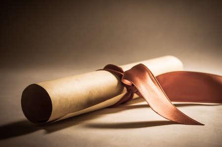 awards: Un diploma de pergamino, enrollado con cinta roja sentado en un �ngulo oblicuo. Procesada para darle una apariencia vintage o retro. Foto de archivo