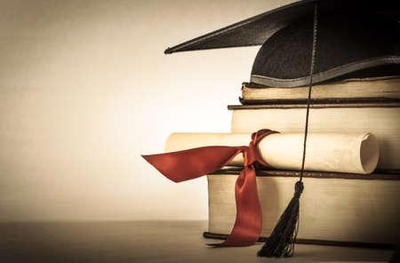 Un mortier et diplôme de défilement, à égalité avec le ruban rouge, sur une pile de vieux livre battue avec un espace vide à gauche. Légèrement sous-saturées vignette pour effet millésime.