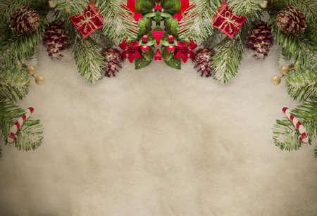 Une bordure de Noël en haut du cadre constitué de feuilles artificielles de pins et d'ornements décoratifs, encadrant le dessus et les côtés du parchemin grungy. Banque d'images