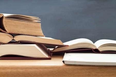 Educazione colpo di vecchi libri impilati aperto per lo studio sulla scrivania in legno con lavagna in background. Archivio Fotografico - 23086242