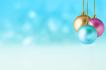 Three Christmas baubles in turquoise, pink and gold, hanging at different lengths in a group against a soft bokeh background of turquoise and white, with the appearance of falling snow.