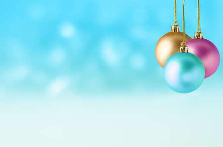 Trois boules de Noël en turquoise, rose et or, suspendus à différentes longueurs d'un groupe sur un fond de bokeh doux de turquoise et blanc, avec l'apparition de la neige qui tombe.