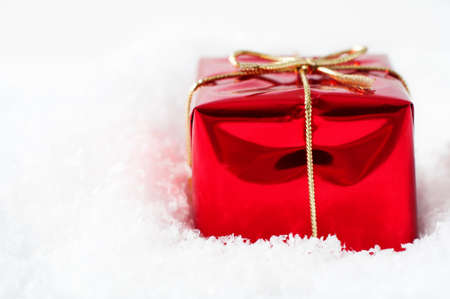 nestled: A single Christmas gift box in shiny red foil wrapping and tied to a bow with gold string ribbon, nestled in artificial white snow with copy space to the right.
