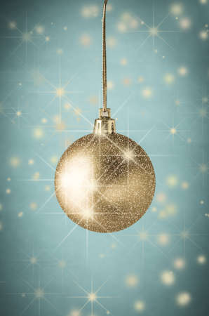 centred: Multimedia image centred around a photograph of a gold bauble, layered with twinkling glitter and sparkling stars against vignetted turquoise blue background scattered with shining gold stars and and soft snowy orbs.