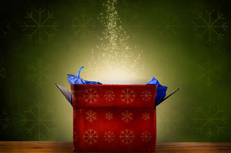 An opened red Christmas gift box with gold snowflake patterns, emitting a magical warm bright glowing light and rising sparkling stars.  Set against a green patterned fabric wallpaper effect on a wooden planked surface. photo