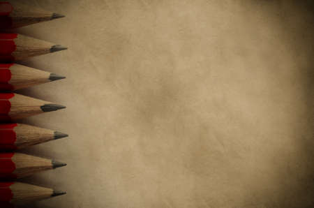 inwards: A column of pencil tips pointing inward, forming a border on the left side of a piece of parchment paper copy space with vignette.  Vintage style image for education or arts background.
