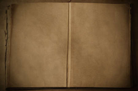 furled: An old vintage book on a wooden table, opened out from its centre to expose blank, parchment coloured pages.  Vignetted, aged image.