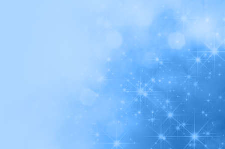 fading: A light blue background with bokeh and sparkling stars, fading towards solid colour copy space on the left side.