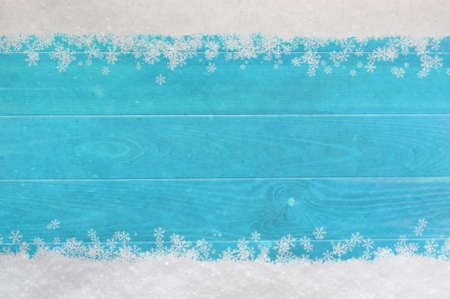 Christmas snow and snowflakes border at top and bottom of light, bright blue wood planking. photo