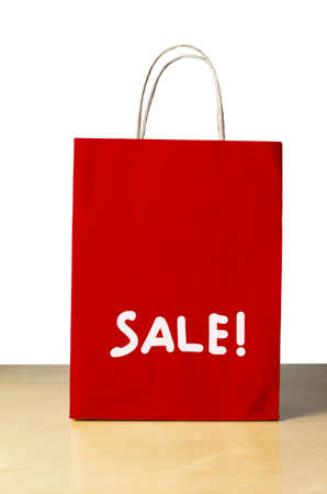economizing: A red carrier bag on a light wood table agianst a white background with the word SALE! written on the lower half in white.