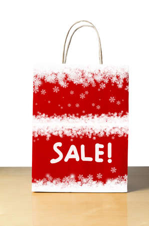 economizing: A red carrier bag on a wooden table against white background, decorated with white snowflake borders with the word SALE! in the lower half for Christmas or Winter sales promotions.