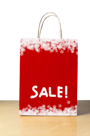 A Winter or Christmas sale shopping bag in red with white snowflake borders at top and bottom, and the word 'SALE!' in the lower half with copy space above i.   photo