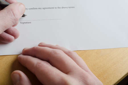 Close up of male hand signing Signature portion on dotted line of a white legal document with cartridge pen nib, while the other hand rests on light wood laminate table. photo