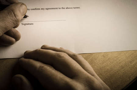 Close up of hands signing document with an austere, vintage feel. Stock Photo