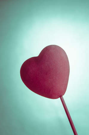 velvety: Soft fabric velvety pink heart on a stick against turquoise background.