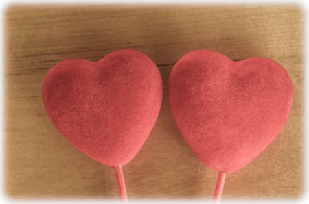 velvety: Two coral pink soft velvety hearts on sticks against a wood background.