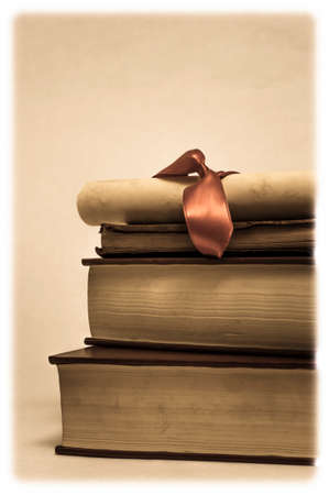 studied: A parchment diploma scroll with red ribbon on top of a stack of old, worn, used books.  Low saturation vintage effect with soft rectangular white vignette to simulate old photograph. Stock Photo