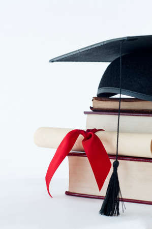 A graduation mortarboard on top of a stack of books, with parchment scroll tied in red ribvon. photo