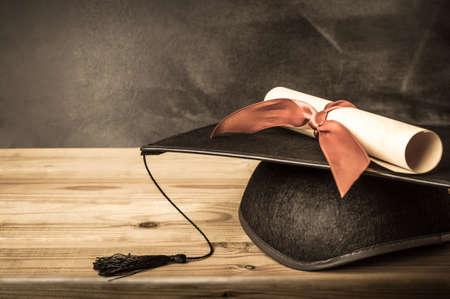 Un rouleau de diplôme lié avec le ruban rouge, reposant sur un mortier de graduation, sur un bureau en bois en face d'un tableau noir d'école. Créé dans le style vintage avec une faible saturation.