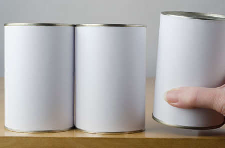 raising cans: Conceptual image of three tin cans with blank white paper labels on a shelf, with middle aged female hand reaching in from right of frame, picking one up to indicate choice or preference.  Empty labels  provide copy space. Stock Photo
