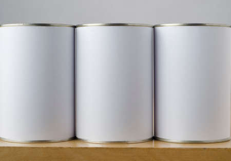 tin: Conceptual image of three tin cans with blank white paper labels on a shelf, copy space on labels allows inclusion of appropriate text or images to indicate options.