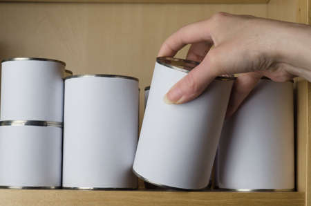 A selection of tin cans in various sizes on a shelf, with female hand reaching in from the right to select one.  Labels are unbranded and blank white for copy space. photo