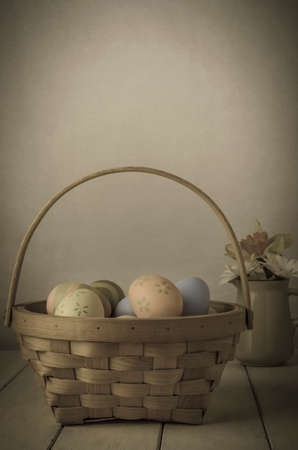 A wiicker basket filled with hand painted Easter eggs on old, shabby planked table with jug  of daffodils and chrysanthemums in background. photo