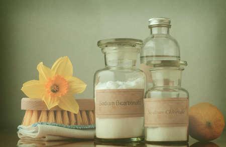 productos naturales: Proceso cruzado todavía la vida de las opciones de limpieza naturales. El bicarbonato de sodio y la sal en frascos de boticario, vinagre blanco detrás de ellos y un limón a la derecha. Una tela doblada y el cepillo de madera de la izquierda están cubiertas con un narciso para significar la limpieza de primavera