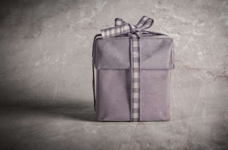 wrapped gift: Vintage style gift box with lid, wrapped in lilac paper and  tied with a bow in gingham (checked) ribbon.
