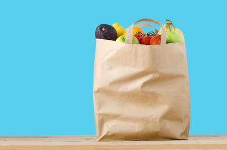A brown paper shopping bag, filled to the top with varieties of fruit, on a light wood surface.  Isolated on a turquoise blue background. photo