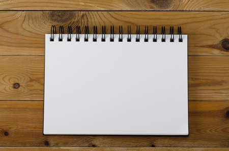 Overhead shot of a spiral notebook, opened on a blank page on wood planked background.