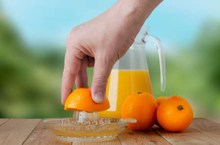 A hand squeezing juice from an orange on a manual glass squeezer.  Set on a wooden planked table with a group of three oranges and a glass jug of juice.  Outdoor background of soft foliage. photo