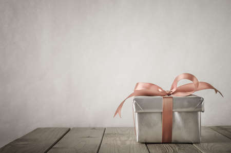 A gift box with closed lid, wrapped in silver paper and tied to a bow with a satin ribbon.  Placed on a weathered old wooden table with copy space behind and above.