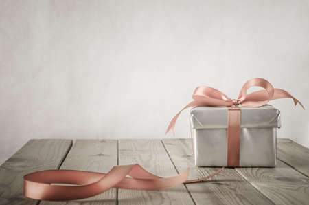 A gift box with closed lid, wrapped in silver paper and tied to a bow with a satin ribbon.  Placed on a weathered old wooden table with copy space behind and above. Cut ribbon remnant to the side.  Stock Photo