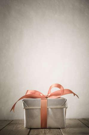 コンピューターを閉じたまま、銀紙に包まれた、サテンのリボンと弓に縛らとギフト ボックスです。 コピーの背後に、上記の領域と風化の古い木製 写真素材