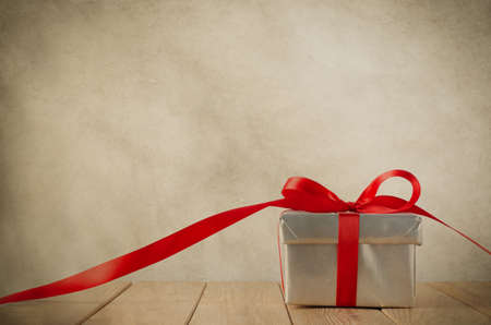gift box: A silver gift box with red ribbon on wood plank table.  Ribbon trails off to the side and faces front.  Old grungy parchment effect gives a vintage feel.  Copy space above and on ribbon.