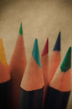 hues: Close up of brightly coloured art pencils with tips pointing upwards.  Retro style image.
