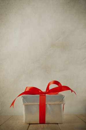 finishing touches: A single silver Christmas gift box, tied to a bow with red satin ribbon, on an old wood plank table with parchment background.  Vintage style. Stock Photo