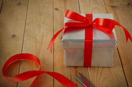 christmas bonus: Gift wrapping scene. A Christmas gift box wrapped in silver paper and tied with red ribbon to a bow, on an old wood plank table with scissors and ribbon remnants.  Vintage style.