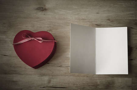 message box: Overhead shot of a painted red wooden heart shaped gift box with ribbon bow, and an opened greeting card, left blank for a message.Vintage effect with vignette gives appearance of old weathered wooden table beneath.